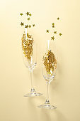 Champagne glasses with glitter on beige background, space for text