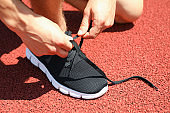 Man tying shoelaces on red athletic running track, close up