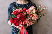 Very nice young woman holding beautiful blossoming flower bouquet of fresh roses, carnations, in passionate red colors on the grey background