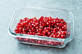 Ripe Pomegranate with Seeds in Glass Bowl.
