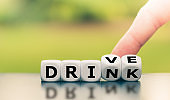 """Drink or drive? Hand turns dice and changes the word """"drink"""" to """"drive"""", or vice versa."""