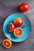 Blood or red oranges  on gray background