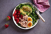 Tuna strawberry avocado egg and spinach salad in bowl
