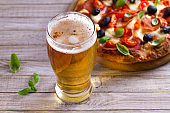Beer and pizza on wooden plate. Ale and  snack
