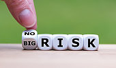 Hand turns a dice and changes the expression 'big risk' to 'no risk'