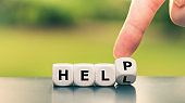 """Getting help concept. Hand turns a dice and changes the word """"hell"""" to """"help""""."""