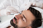 Calm bearded man undergoing plucking eyebrows procedure