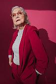 Waist up of fashionable confident elderly woman wearing modern eyeglasses in studio