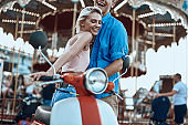 Two people with motorbike laughing near the merry-go-round
