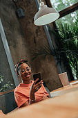 Young afro-american woman is holding mobile phone