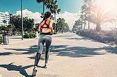 Sporty slender girl jogging on seafront road