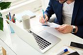 Businessman inserting amendments in working documentation