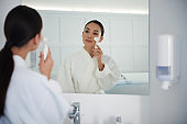 Young asian lady cleaning face with brush