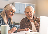 Happy old man and woman planning retirement with computer