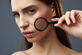 Attractive girl demonstrating perfect skin through magnifying glass