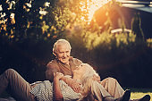 Relaxed elderly couple locating outside on lawn