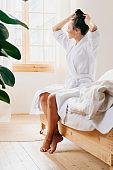 Beautiful young woman wearing bathrobe at home