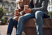 Couple in jeans sitting with cups of coffee stock photo
