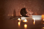 Young lady enjoy relaxed spa bath with candle