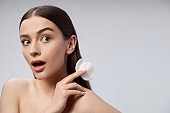 Surprised woman is using cosmetic cotton disc