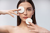 Thoughtful woman is holding cosmetic cotton disc