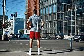 Sportive man standing on street near crosswalk