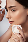 Beautiful female is holding cosmetic cotton discs in studio