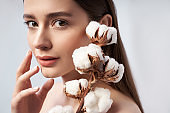 Thoughtful woman holding branch of decorative cotton