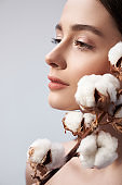 Calm woman with branch of decorative cotton in studio