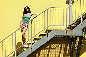 Beautiful brunette girl standing on stairs against yellow wall