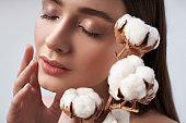 Pretty lady with branch of decorative cotton in studio