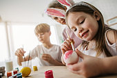 Low angle of little girl painting Easter egg in kitchen