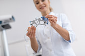 Smiling ophthalmologist in white lab coat holding optical trial lens frame