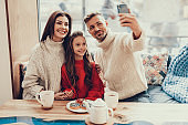 Happy family taking sweet selfie in cafe