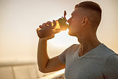 Good-looking young male athlete drinking water outdoors