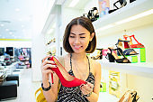 Woman customer trying on chosen red shoes in store