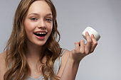 Cheerful teen girl with perfect skin demonstrating cosmetic product
