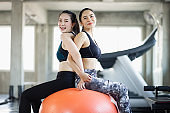 Group attractive asian woman stretching the muscles and relaxing after exercise, workout, fitness at gym club. Sports recreation glad smiling girl is enjoy with her training process.
