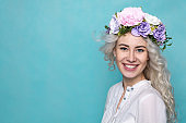 Young Beautiful Woman in Flower Wreath with Wavy Blond Hair. Spring. Studio. Copy Space