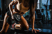 Sporty tanned woman with perfect shape lifting dumbbells in the gym. Close up