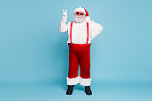 Full size photo of fat funky funny santa in hipster eyewear with funny big abdomen belly make v-sign enjoy christmas noel time wear overalls red suspenders isolated over blue color background