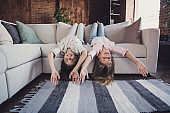 Two nice lovely attractive charming different cheerful cheery friendly girls lying on divan upside-down having fun day in house loft industrial interior style