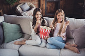 Portrait of two nice sweet lovely attractive lovable fascinating charming cheerful cheery girls sitting on divan enjoying video film movie cinema in house loft industrial interior style