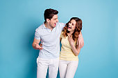 Photo of bonding pair hugging listen humorous story having fun wear casual t-shirts pants isolated blue background