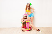 Pretty hipster woman siting on floor with skate near her sister