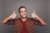 Cheerful man with beaming smile showing thumbs up