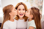 Close-up portrait of nice cute lovely winsome sweet gentle tender attractive charming cheerful cheery positive glad redhair people mom kissing pre-teen girls in house indoors