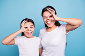 Close up photo beautiful two people brown haired mom little daughter friends look finger specs okey symbol silly screaming shouting wear white t-shirts isolated bright blue background