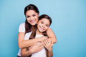 Close up photo amazing pretty two people brown haired mum mom small little daughter stand hugging piggy back lovely free time rejoice wearing white t-shirts isolated on bright blue background