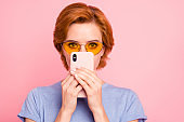 Close-up portrait of her she nice cute charming attractive lovely winsome teen girl wearing casual blue t-shirt yellow glasses hiding reading sms message isolated on pink pastel background
